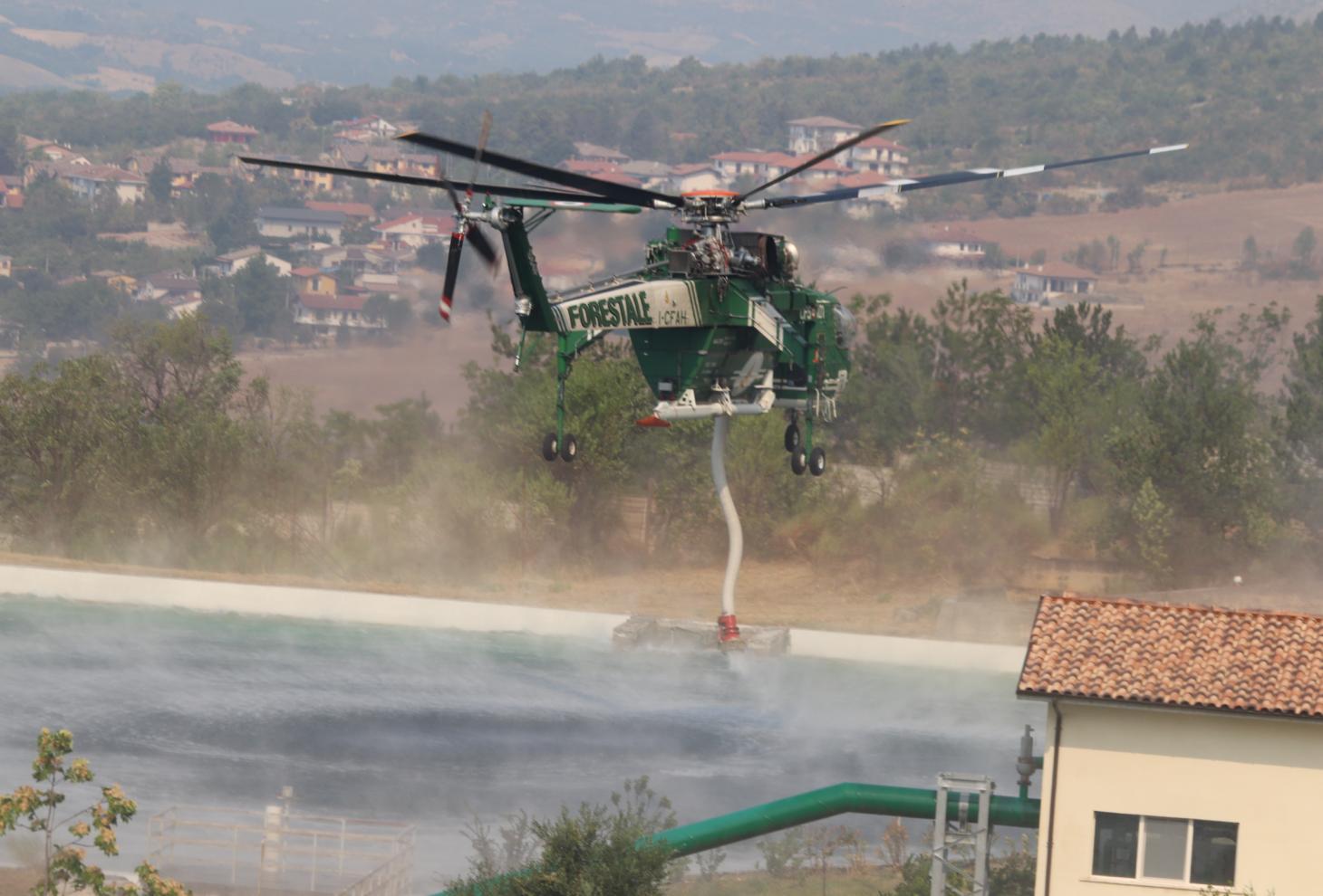 L'Erickson AirCrane S-64F carica circa 10.000 litri di acqua dalle due vasche in località Fonte d'Amore (Sulmona)